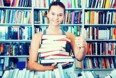 Muchacha del adolescente que sostiene una pila de libros en librería Fotos de archivo