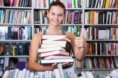 Muchacha del adolescente que sostiene una pila de libros en librería Fotos de archivo libres de regalías