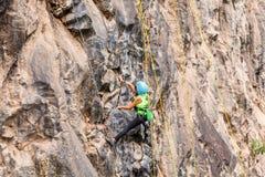 Muchacha del adolescente que sube una pared vertical de la roca Imagenes de archivo