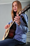 Muchacha del adolescente que toca la guitarra Imagen de archivo