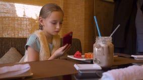 Muchacha del adolescente que usa el teléfono elegante para el rollo de sushi móvil de la foto en café japonés almacen de video