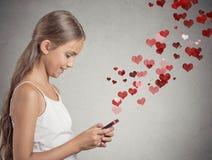 Muchacha del adolescente que usa mandar un SMS en el teléfono elegante Imagenes de archivo