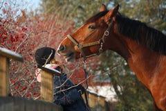 Muchacha del adolescente y caballo de bahía que se abraza Imagenes de archivo