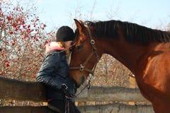 Muchacha del adolescente y caballo de bahía que se abraza Imágenes de archivo libres de regalías