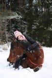 Muchacha del adolescente y caballo marrón que mienten en la nieve Fotografía de archivo