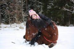 Muchacha del adolescente y caballo marrón que mienten en la nieve Imágenes de archivo libres de regalías