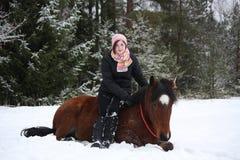 Muchacha del adolescente y caballo marrón que mienten en la nieve Imagenes de archivo