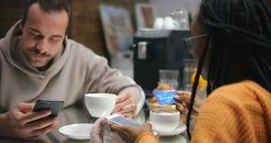 Muchacha del Afro con el novio que usa el teléfono para las compras en línea con la tarjeta de crédito almacen de video