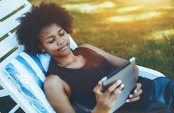 Muchacha del Afro con la tableta digital al aire libre en el recliner Fotos de archivo libres de regalías
