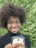 Muchacha del Afro que escucha la música en un parque Imágenes de archivo libres de regalías