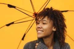 Muchacha del afroamericano con el paraguas amarillo Foto de archivo libre de regalías