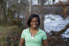 Muchacha del afroamericano delante del río foto de archivo libre de regalías
