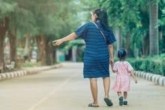 Muchacha del alumno de la mam? y de la hija que se sostiene de com?n acuerdo en la calle para ir a la sala de clase imagen de archivo libre de regalías