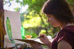 Muchacha del artista del adolescente todavía que pinta vida con la botella verde en el aire llano fotos de archivo libres de regalías