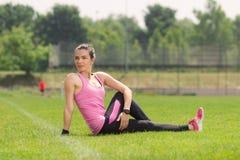 Muchacha del atleta que estira la hierba Imagenes de archivo