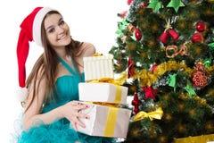 Muchacha del ayudante de Papá Noel con la pila de presentes debajo del árbol de navidad Fotografía de archivo