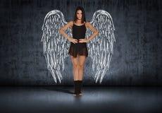 Muchacha del bailarín con las alas que dibujan en la pared en viejo Fotos de archivo