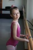 Muchacha del ballet que se coloca al lado de la barra Fotografía de archivo libre de regalías