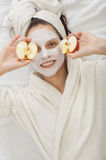 Muchacha del balneario en máscara facial del krem con la manzana foto de archivo