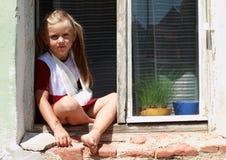 Muchacha del barefeet que se sienta en una ventana con la mano quebrada Imagen de archivo libre de regalías