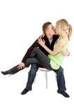 Muchacha del beso del hombre joven en silla fotos de archivo