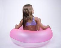 Muchacha del bikini en un flotador en ella detrás fotografía de archivo