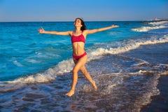 Muchacha del bikini que corre al agua de la orilla de la playa imagen de archivo