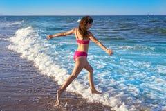 Muchacha del bikini que corre al agua de la orilla de la playa foto de archivo libre de regalías