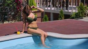Muchacha del bikini que se relaja en el borde de la piscina almacen de video