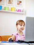 Muchacha del cabrito con la computadora portátil Fotografía de archivo libre de regalías