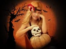 Muchacha del cabrito de Víspera de Todos los Santos con la sonrisa de la calabaza y del cráneo Foto de archivo libre de regalías
