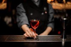 Muchacha del camarero que sirve un cóctel rojo transparente en el vidrio adornado con un ánimo de limón en el contador de la barr fotos de archivo libres de regalías