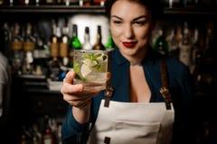 Muchacha del camarero que sostiene un cóctel fresco con la cal y la menta fotografía de archivo