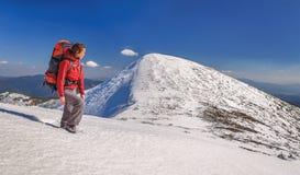 Muchacha del caminante con la mochila en altas montañas Imagen de archivo