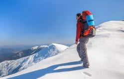 Muchacha del caminante con la mochila en altas montañas Imagen de archivo libre de regalías