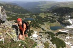 Muchacha del caminante que sube encima de la montaña Fotografía de archivo libre de regalías