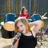 Muchacha del cantante de los niños que canta jugando la banda viva en patio trasero fotografía de archivo