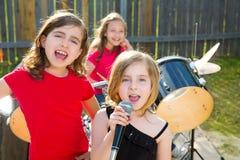 Muchacha del cantante de los niños que canta jugando la banda viva en patio trasero imagen de archivo