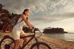 Muchacha del ciclista con la mochila disfrutando de la vista de la isla hermosa Fotos de archivo libres de regalías