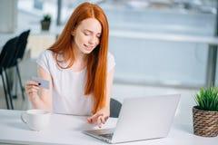 Muchacha del comprador que compra en línea con un ordenador portátil y una tarjeta de crédito Imagen de archivo libre de regalías