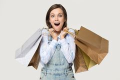 Muchacha del comprador que sostiene montones de los bolsos de compras aislados en gris fotos de archivo