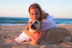 Muchacha del concepto de la amistad con su perro que miente al aire libre Imágenes de archivo libres de regalías