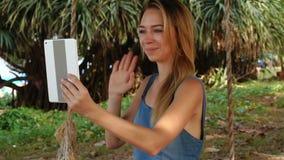 Muchacha del contable de la cámara lenta que usa la tableta para comunicar con los amigos almacen de metraje de vídeo