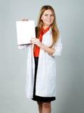 Muchacha del cosmetólogo en un traje blanco, con una hoja limpia en su mano Fotos de archivo libres de regalías