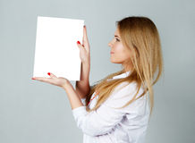Muchacha del cosmetólogo en un traje blanco, con una hoja limpia en su mano Fotos de archivo