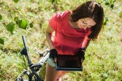 Muchacha del deporte en la tableta digital del control de la bicicleta Imagen de archivo libre de regalías