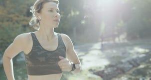 Muchacha del deporte que corre en el parque de la ciudad que lleva Smartwatch y los auriculares inalámbricos almacen de metraje de vídeo