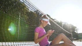 Muchacha del deporte que se sienta en una pista de tenis cerca de red y que usa el teléfono elegante almacen de video