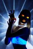 Muchacha del disco con danza del maquillaje del resplandor en luz UV Imágenes de archivo libres de regalías
