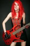 Muchacha del eje de balancín del Redhead con la guitarra baja Imagenes de archivo